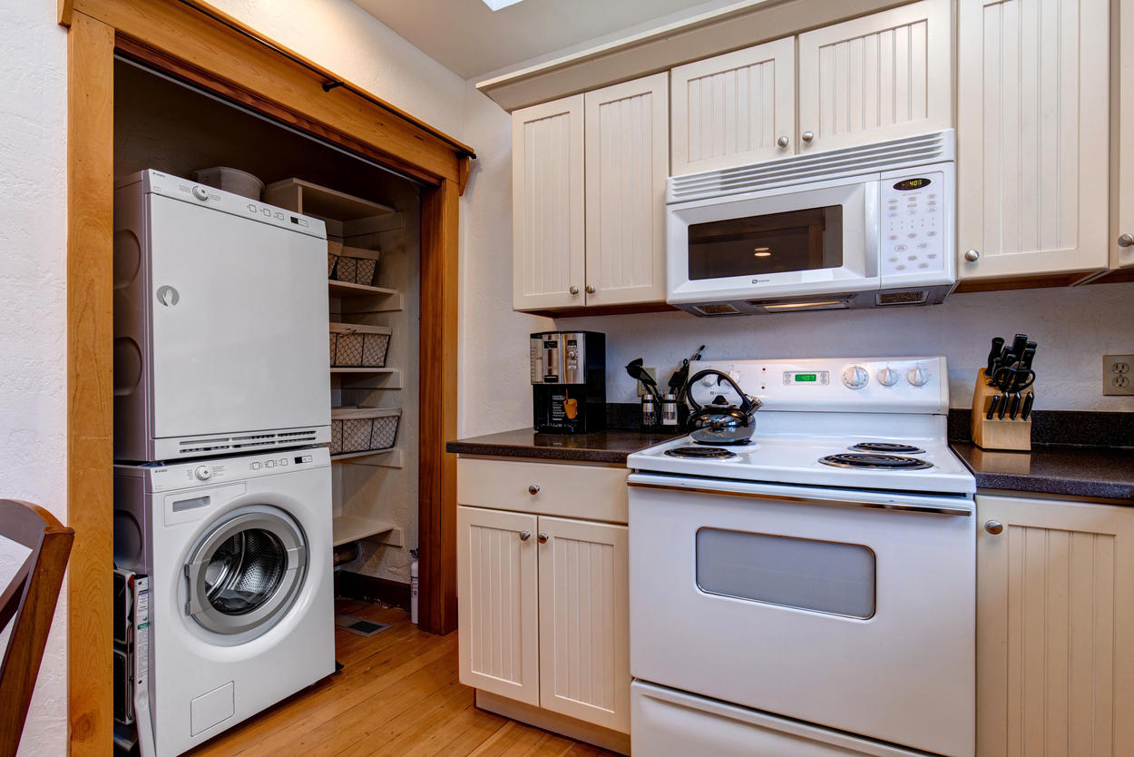 In the kitchen, an efficiency washer and dryer is ready for you to use.