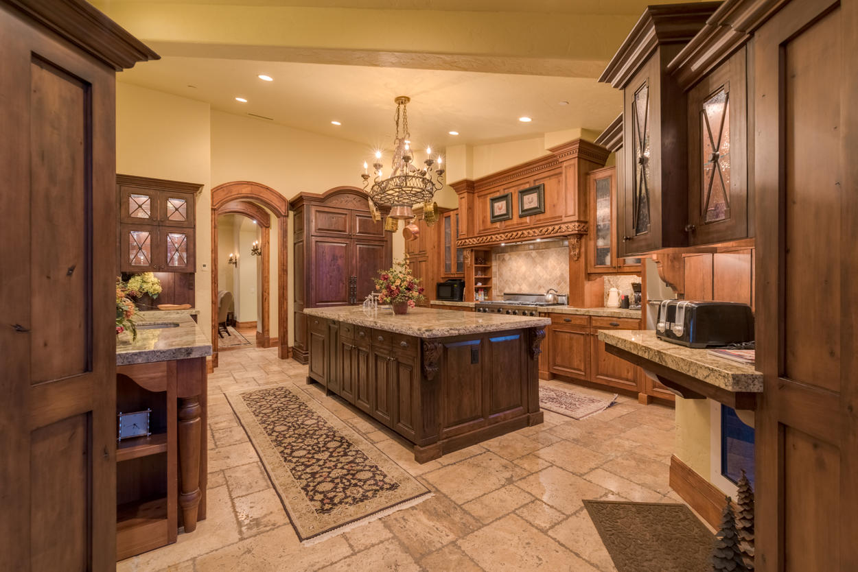 The impeccably detailed kitchen features warm lighting and tons of space