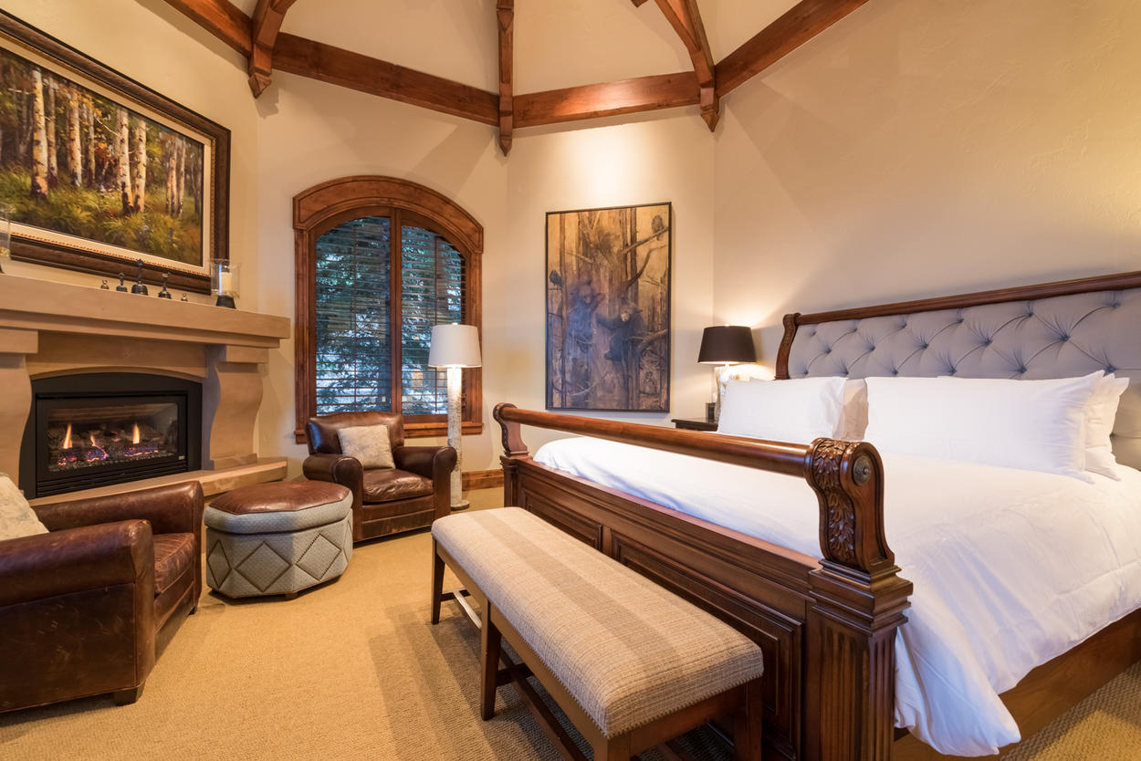 The master features a King sleigh bed, gas fireplace, and soft leather armchairs