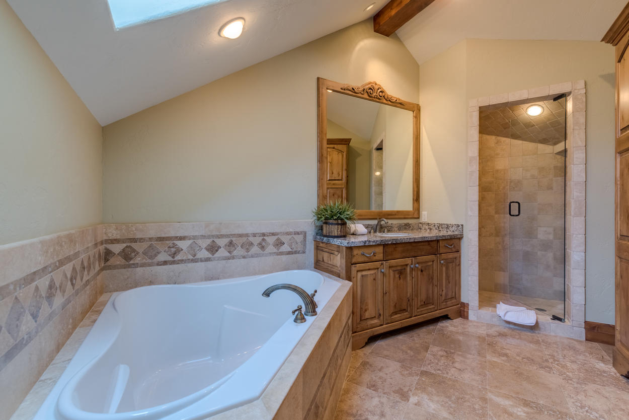 The ensuite for this master has a step-in shower and standalone soaking tub
