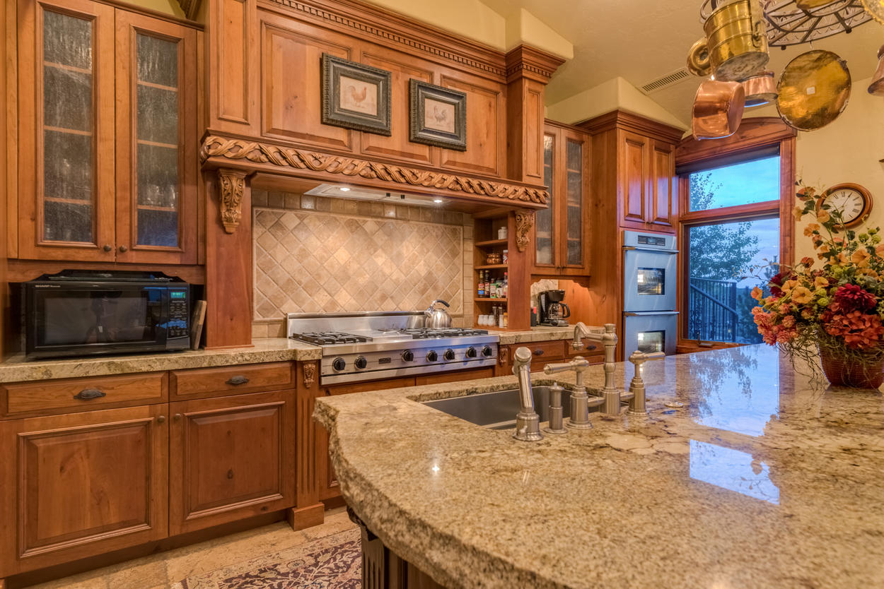 Granite counters top the custom wood cabinetry, including on the kitchen island