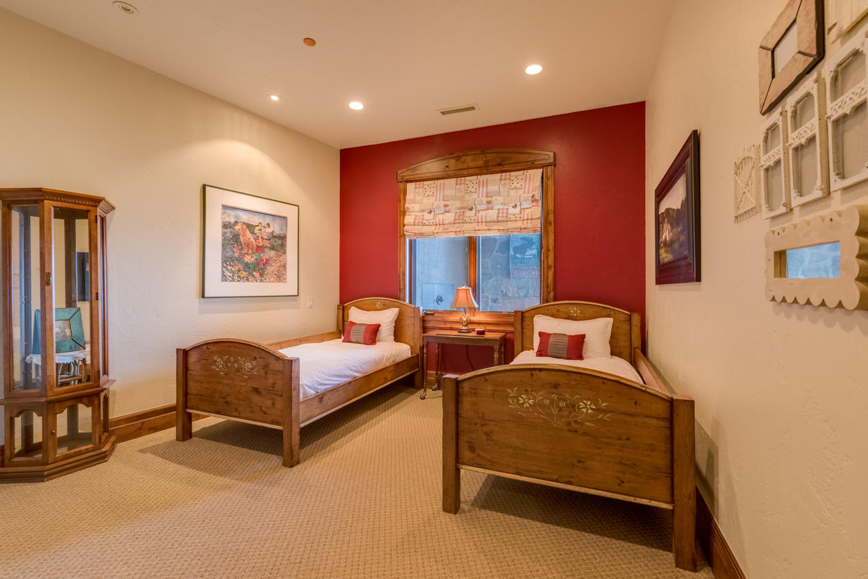 Down one floor from the main living level, the twin bedroom features two twin beds