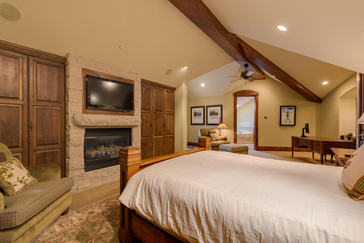 Upstairs, another master suite awaits, featuring a queen bed, gas fireplace, and flat screen tv