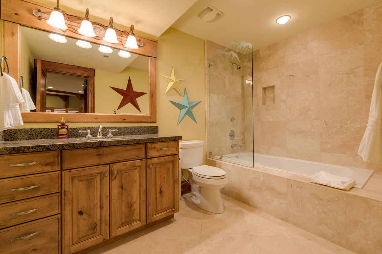 The guest bathroom continues the western theme with a tub/shower combo and wood-trimmed vanity