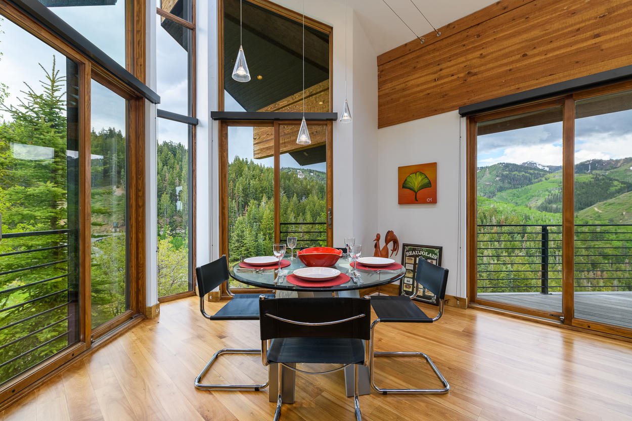 A separate breakfast area features a table for four surrounded by stunning mountain vistas.