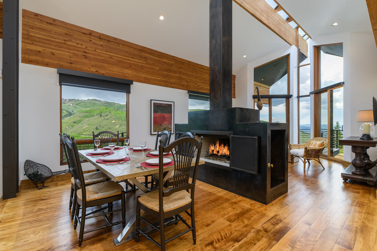 The dining area has a table for six guests next to a contemporary fireplace.