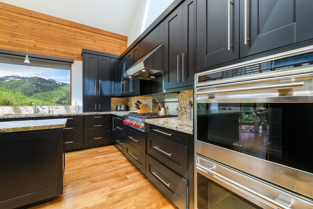The kitchen features a 6-burner gas stove, double oven, and sleek modern designs.