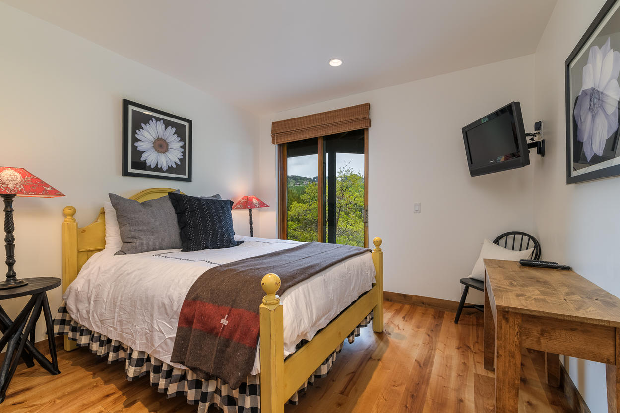 The third guest bedroom has a queen-size bed and views across the patio to the mountains.