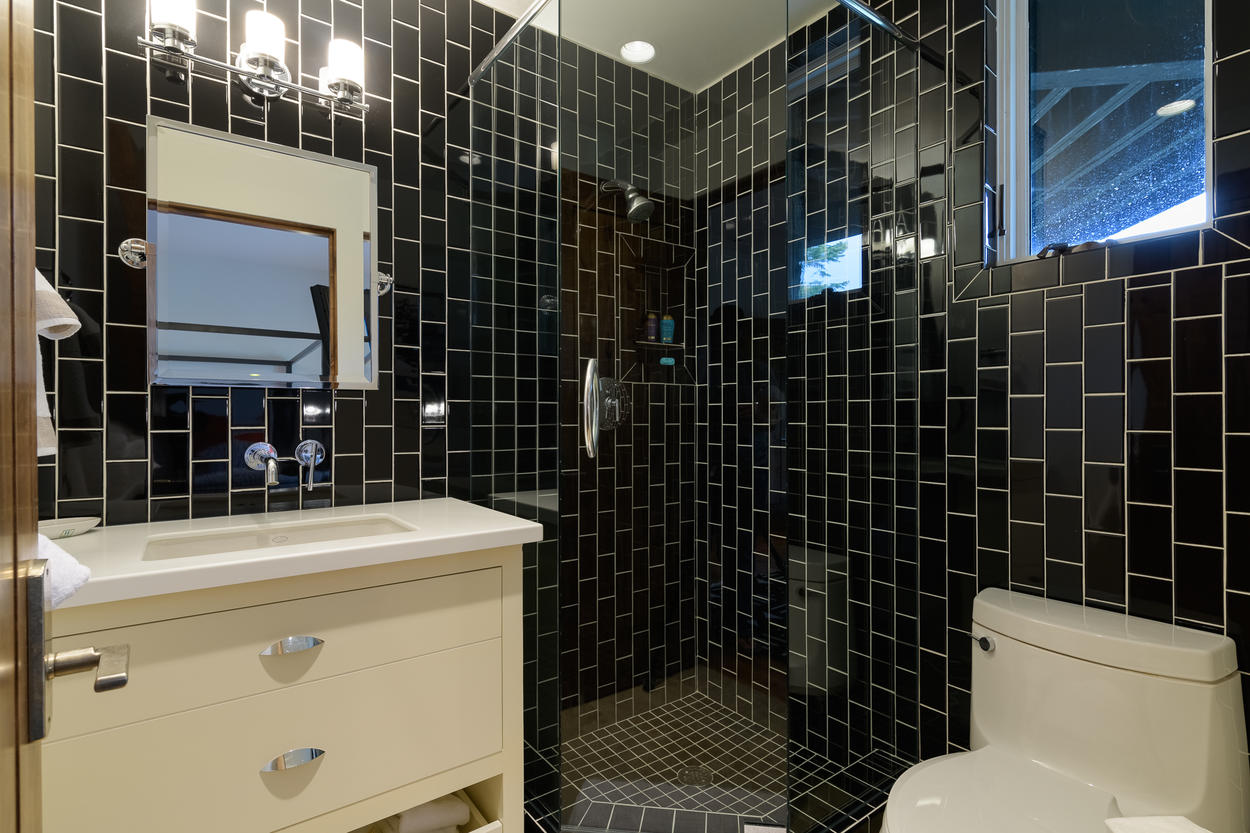 The second bedroom's attached ensuite has a single sink and stand-alone glass shower.