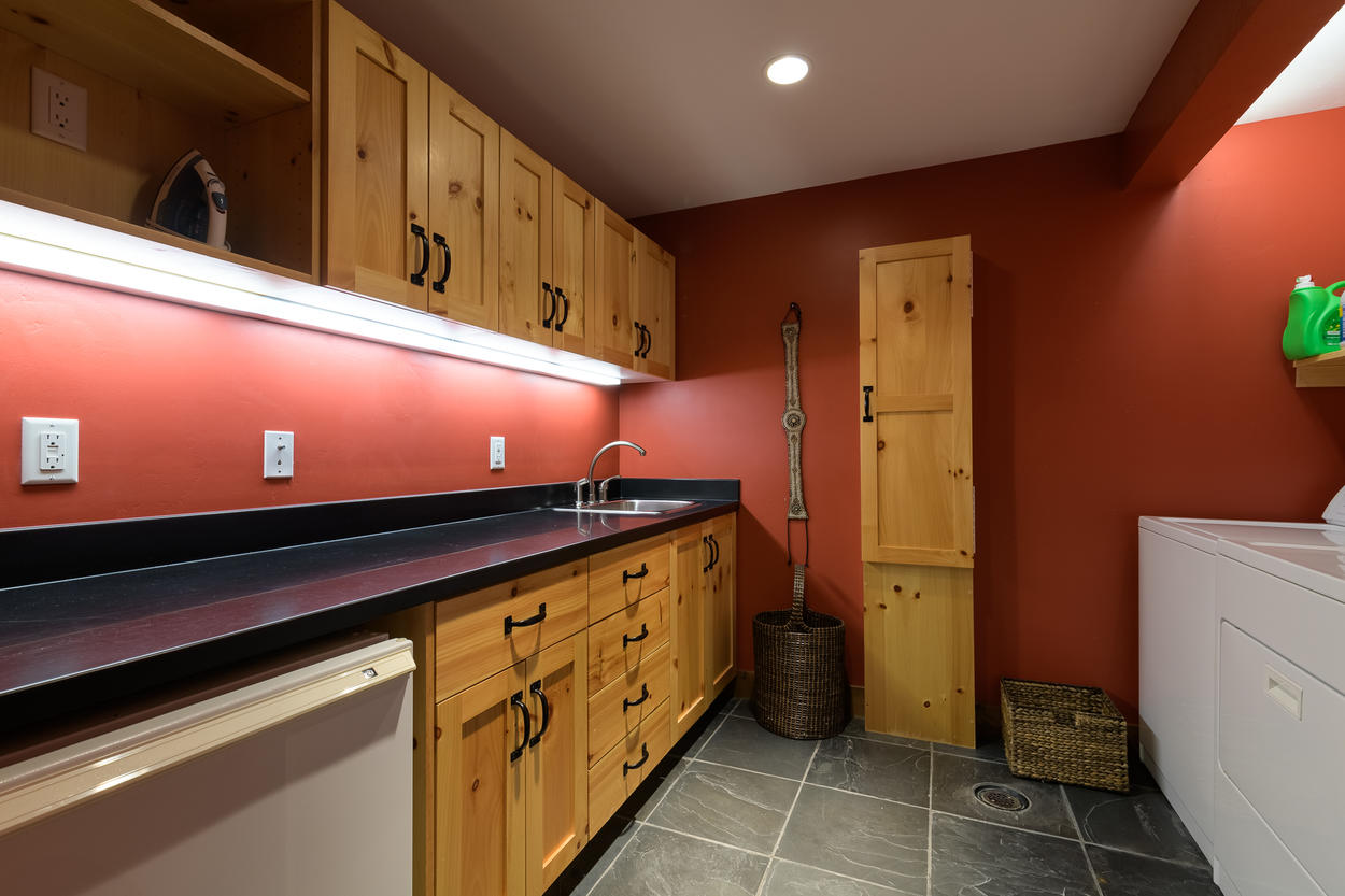In the laundry room you'll find a washer, dryer, sink, ironing board, and plenty of storage.