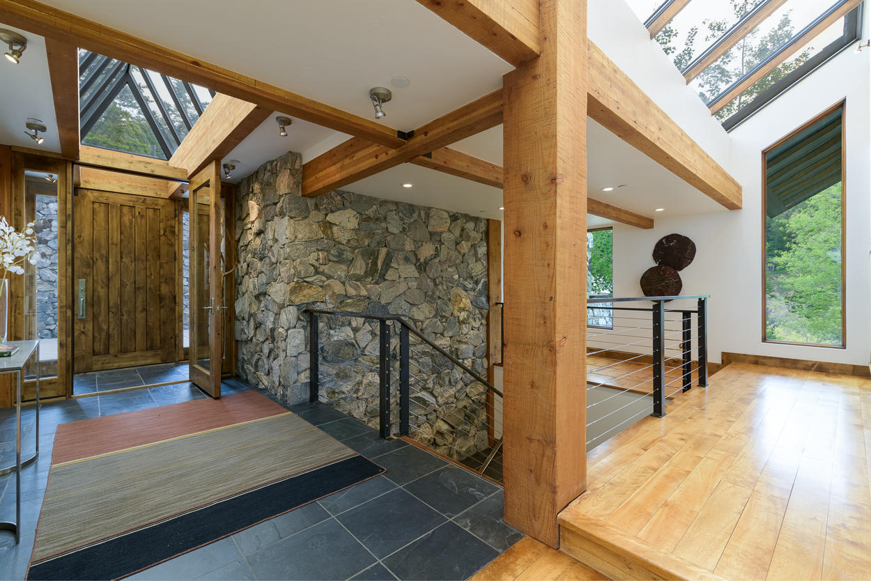 The entryway is highly modern, yet still warm with stone and exposed wood beam construction.