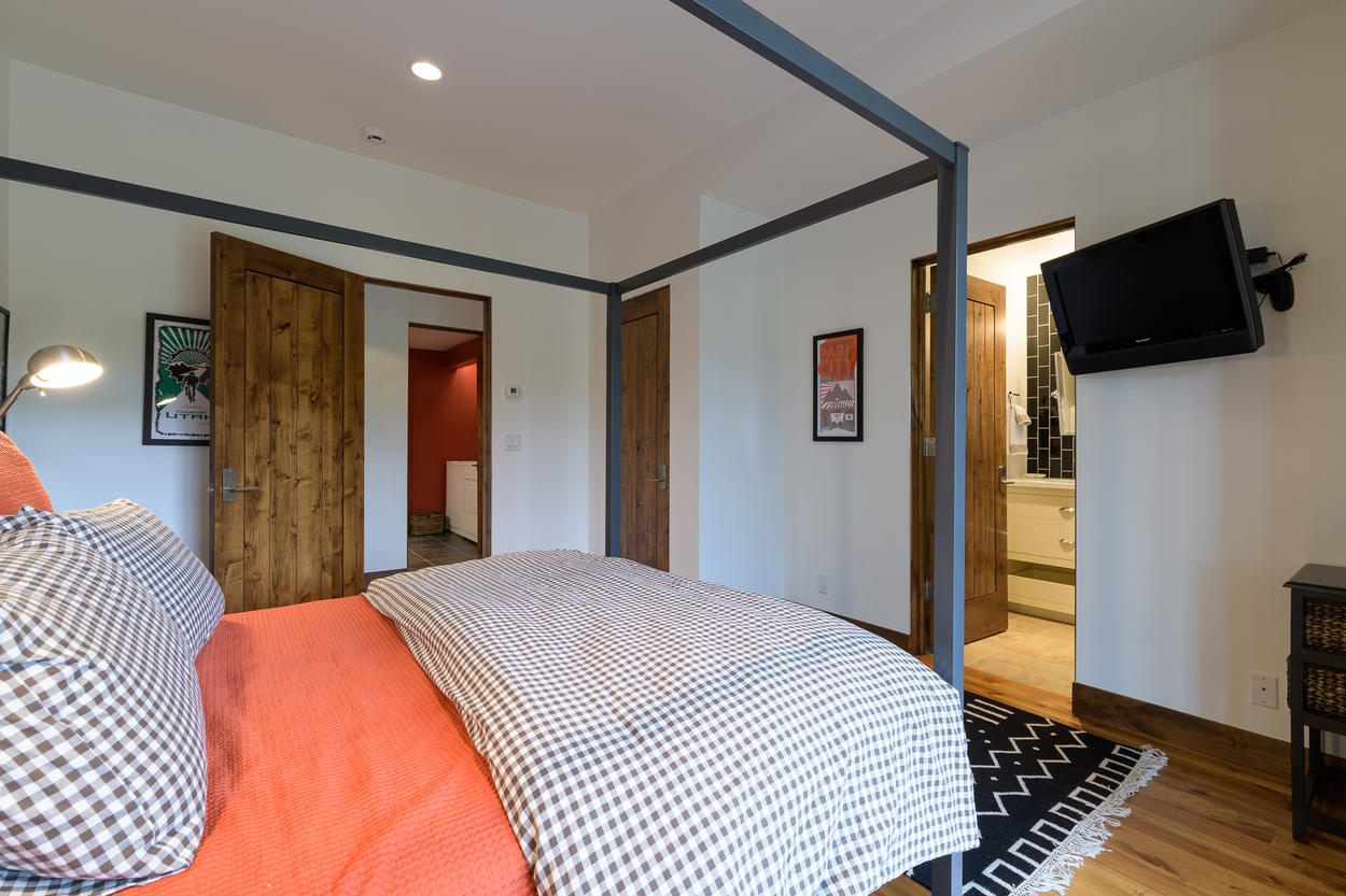 The second guest bedroom features a modern canopy, and a mounted flat screen TV.