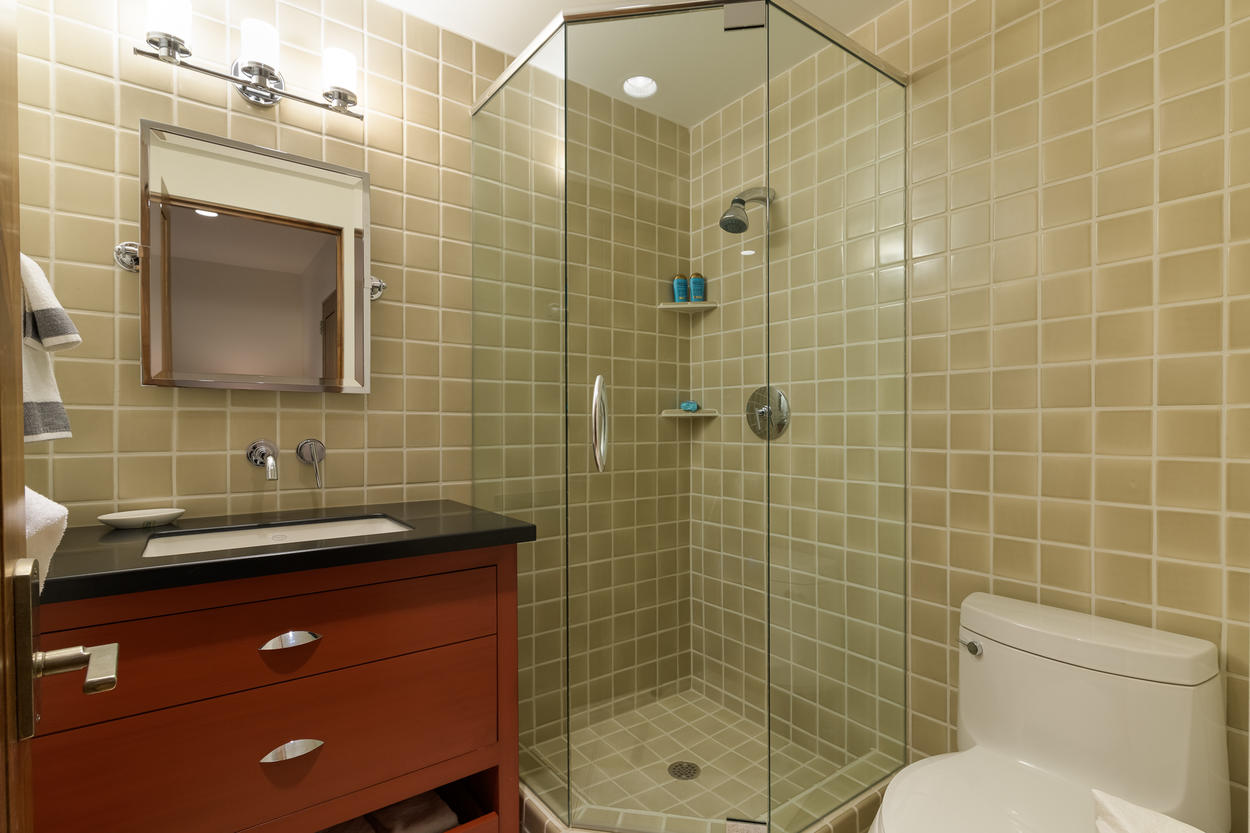 The third guest bedroom's attached ensuite bathroom has a single sink and a glass stand-alone shower.