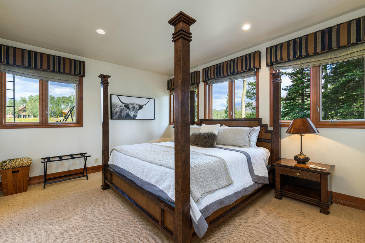 The second Lower Level King bedroom has a king-size bed surrounded by large windows.