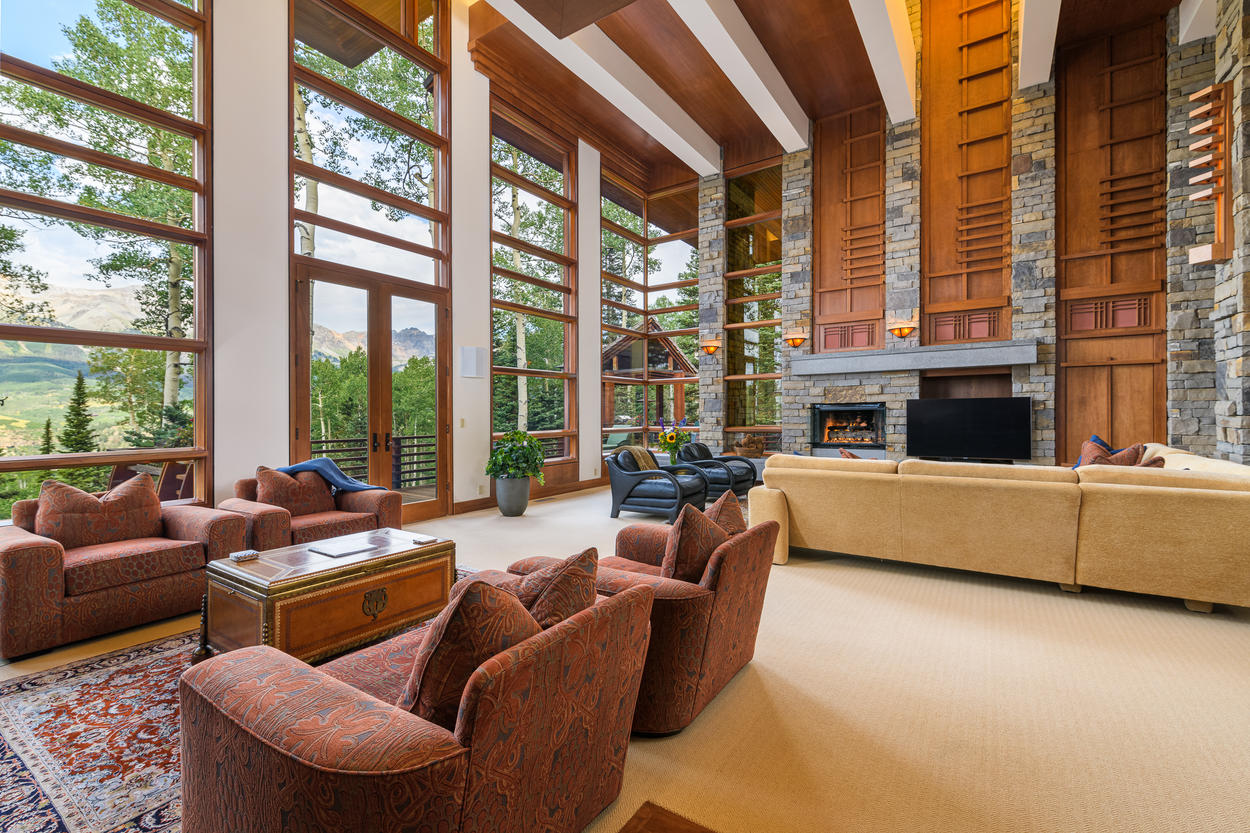 The main living area has two-story windows that illuminate the room in natural light.