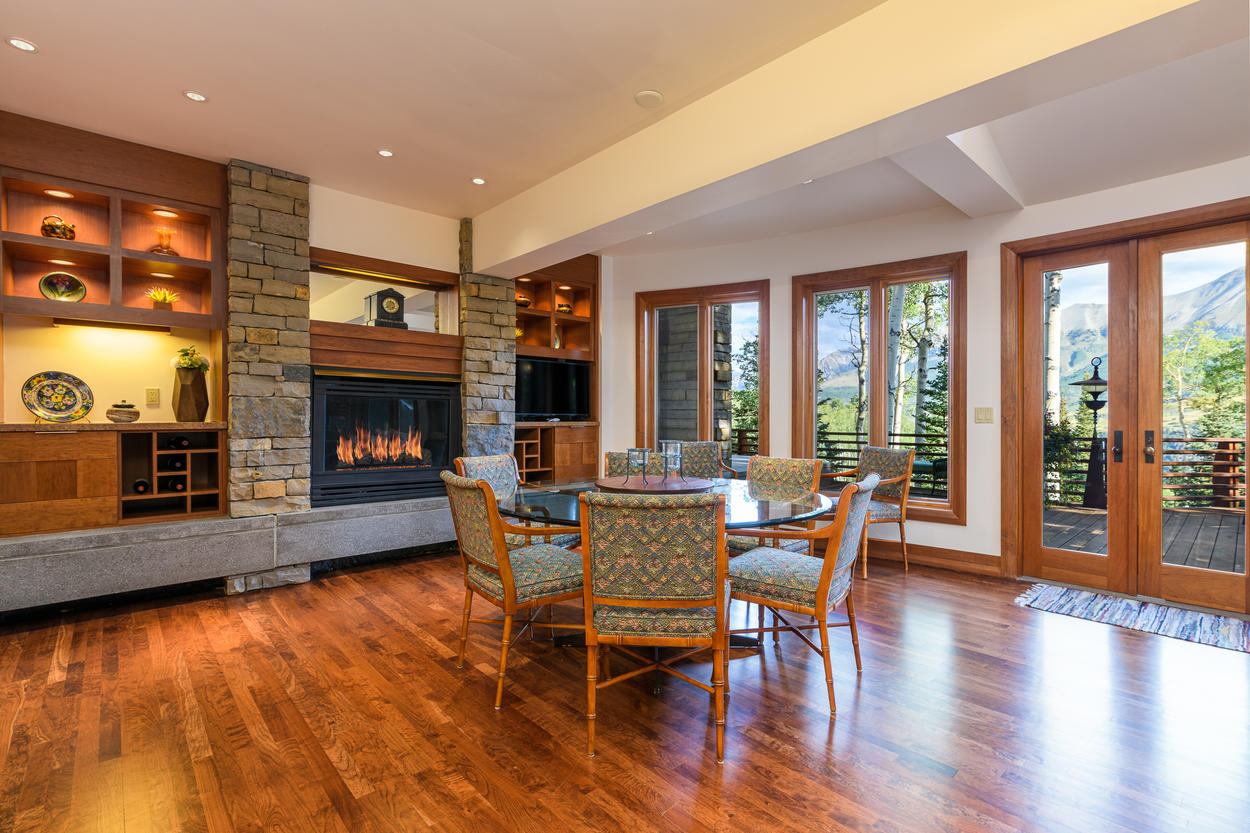 The dining area is set in front of a large gas fireplace, and also has deck access.
