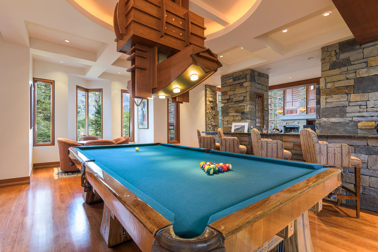 The game room has its own bar with seating for four guests.