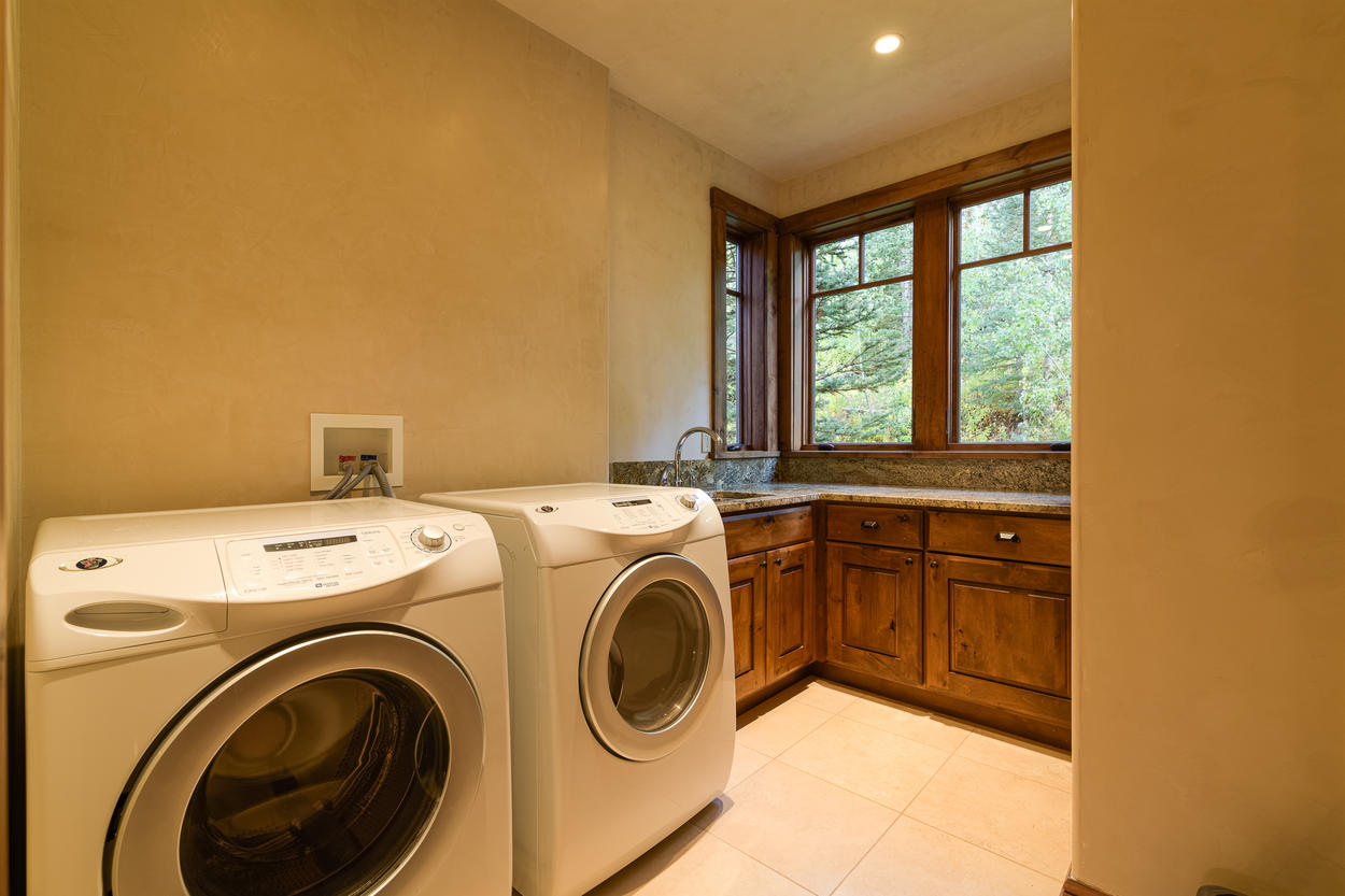 The laundry room is located on the main level and features a washer, dryer, sink, and storage.
