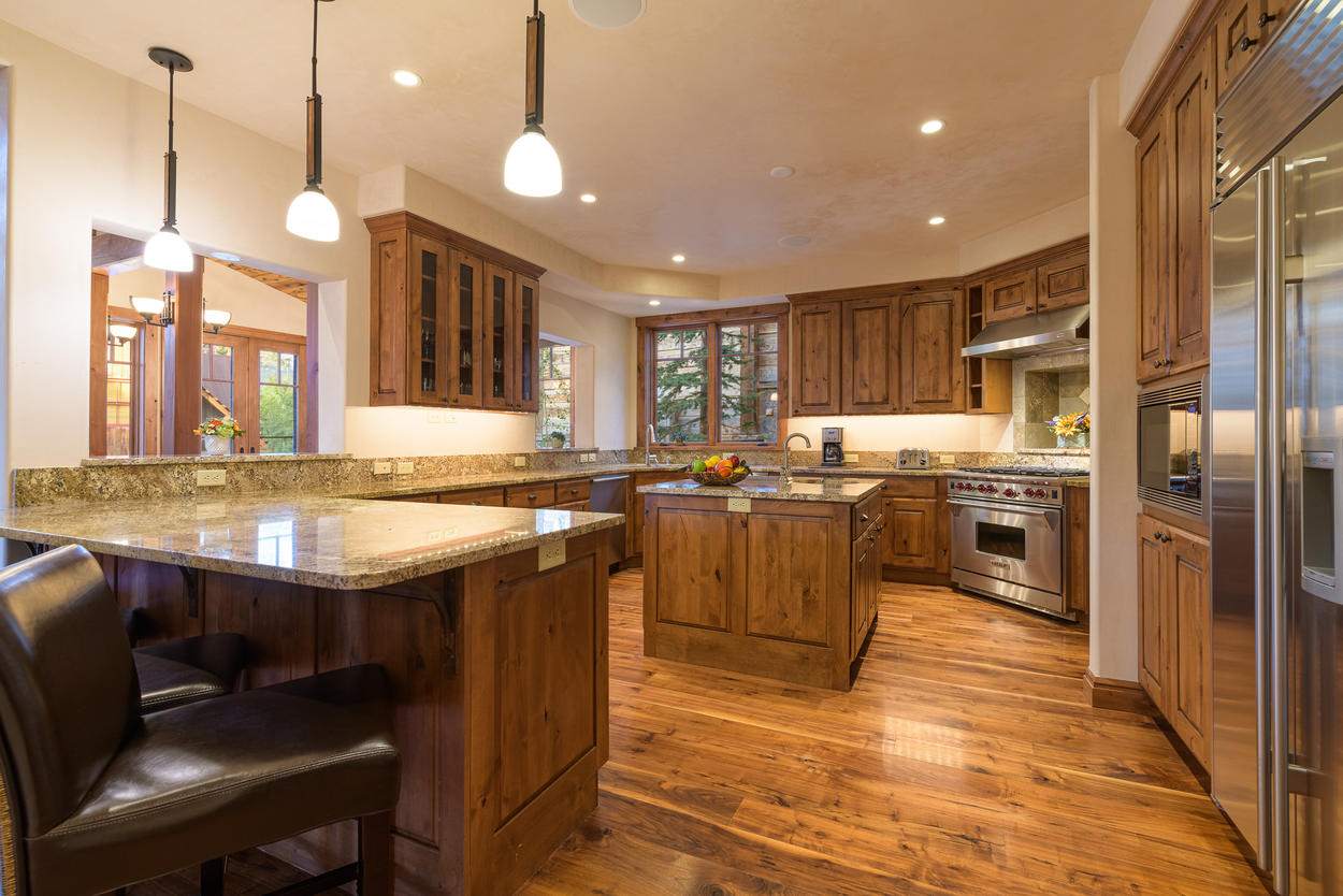 The kitchen is expansive, and looks into the main living area through a bar cutaway.