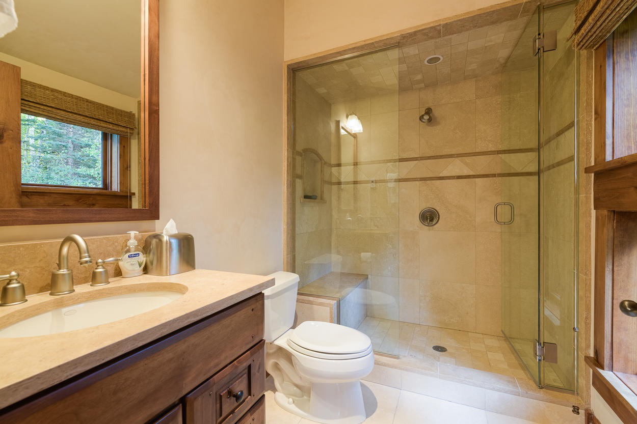 The Trundle Room's ensuite has a frameless glass shower and a single sink.