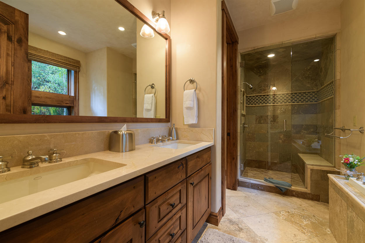 The ensuite to the main level Queen Room has a large walk in shower, a tub, and a double vanity.
