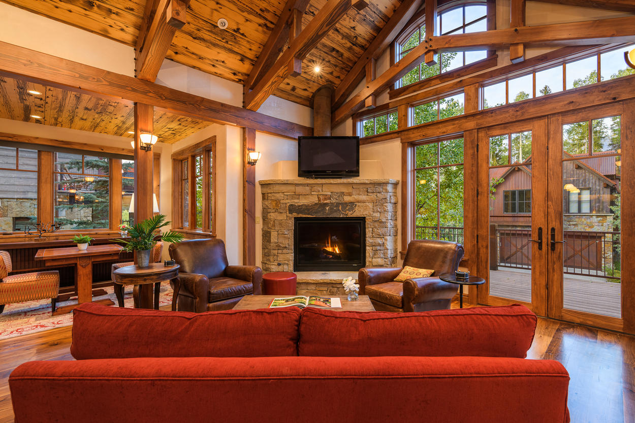 The main living room has vaulted ceilings, a gas fireplace, a TV, and plenty of plush seating.