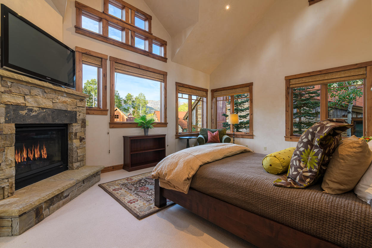 The upper level Master Bedroom has a Queen bed, picture windows, and a large gas fireplace.