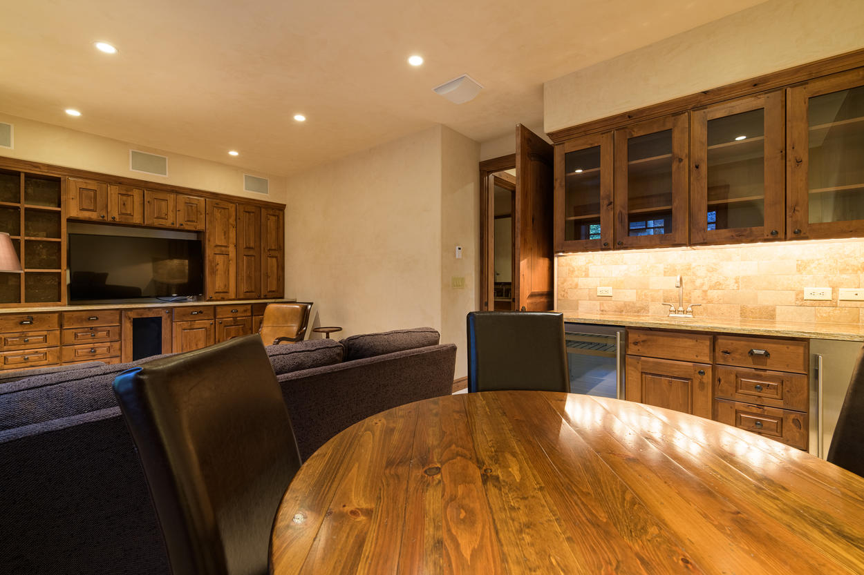 The lower level media room has a wet bar, wine fridge, and card table.