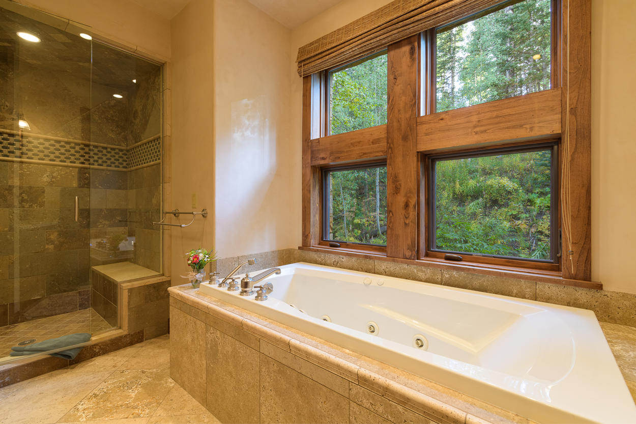 The main level Queen Room has a large jetted tub that looks out into the forest.