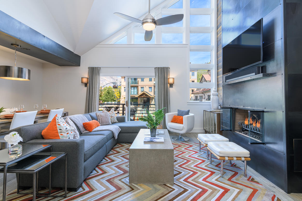 The Great Room has vaulted ceilings, a sleek modern fireplace, and a large flatscreen TV.