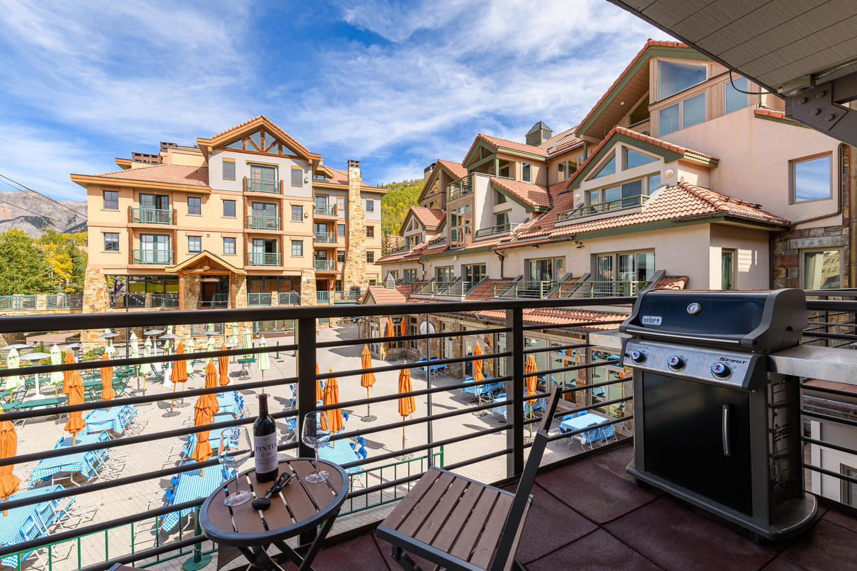 The balcony features a bistro set and a gas grill.