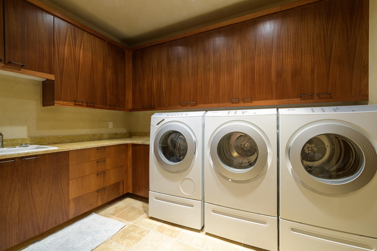 The laundry room is located on the first floor and has 1 washer, 2 dryers, a sink, and plenty of storage.