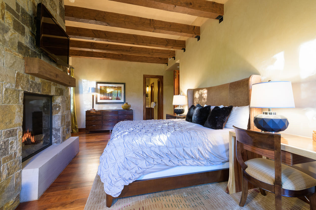 The 1st floor king guest bedroom is extremely cozy, with natural wood beams and sturdy stone.