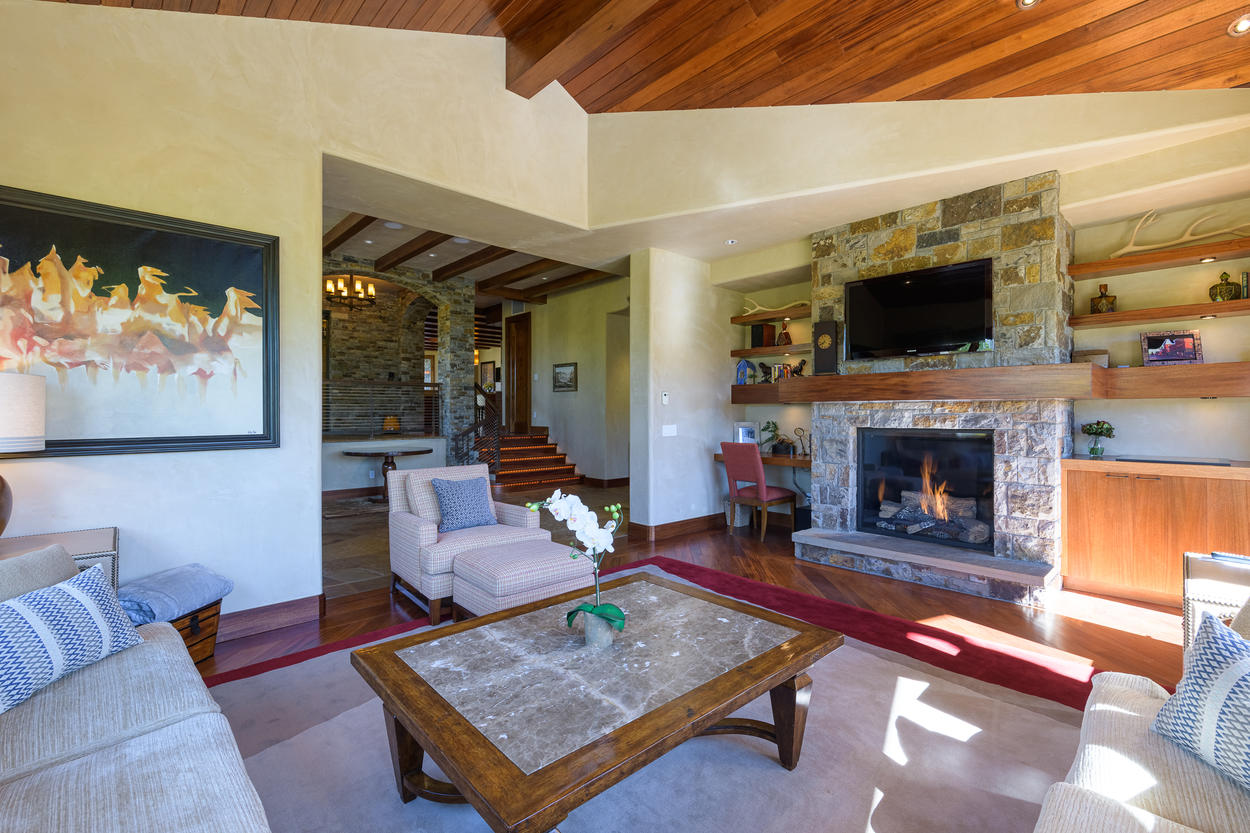 On the second floor, there's a cozy family room with another fireplace and wall-mounted TV.