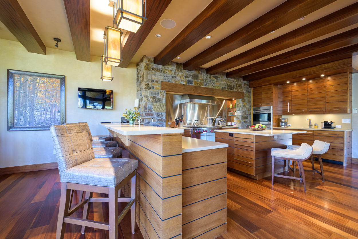 The breakfast bar separates the kitchen from the dining area, and features a wall-mounted TV.