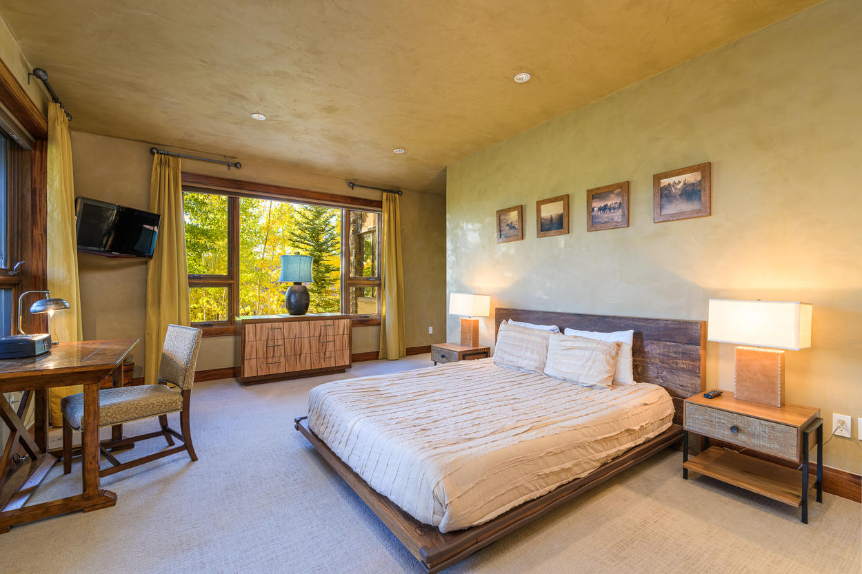 The queen guest bedroom is located on the first floor and has its own TV and forest views.