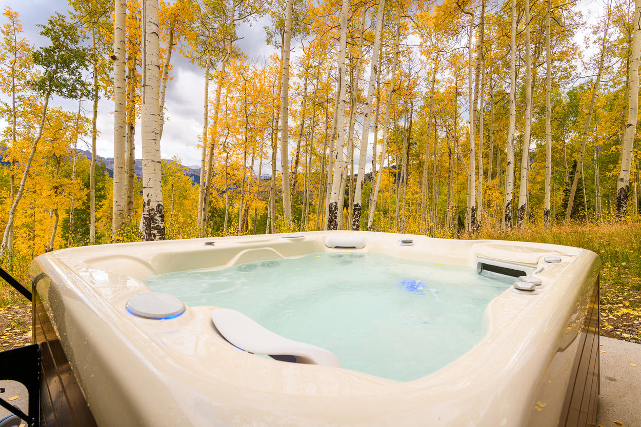 The hot tub, located on the lower patio, is surrounded by large aspens.