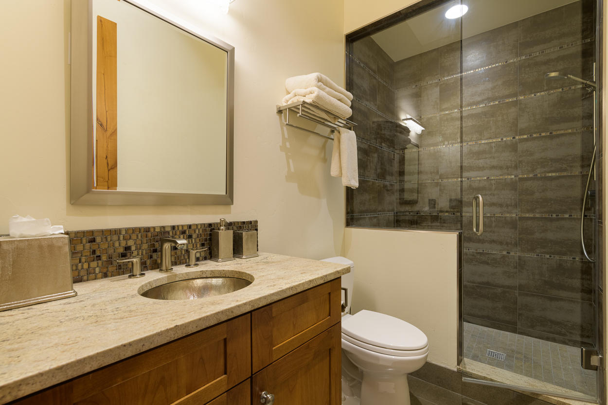 The Queen Guest Bedroom ensuite has a walk-in shower and single sink.