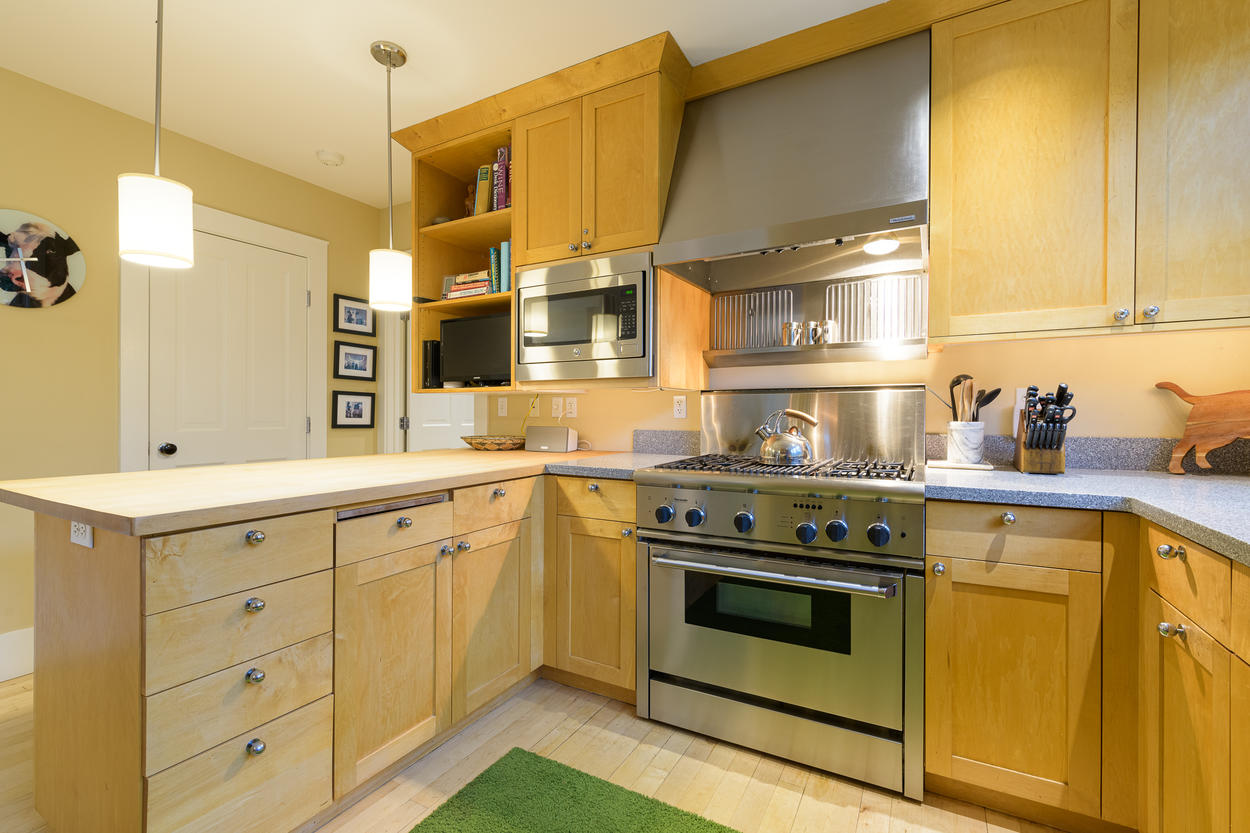 The kitchen features a stainless steel 5-burner gas stove and plenty of counter space.