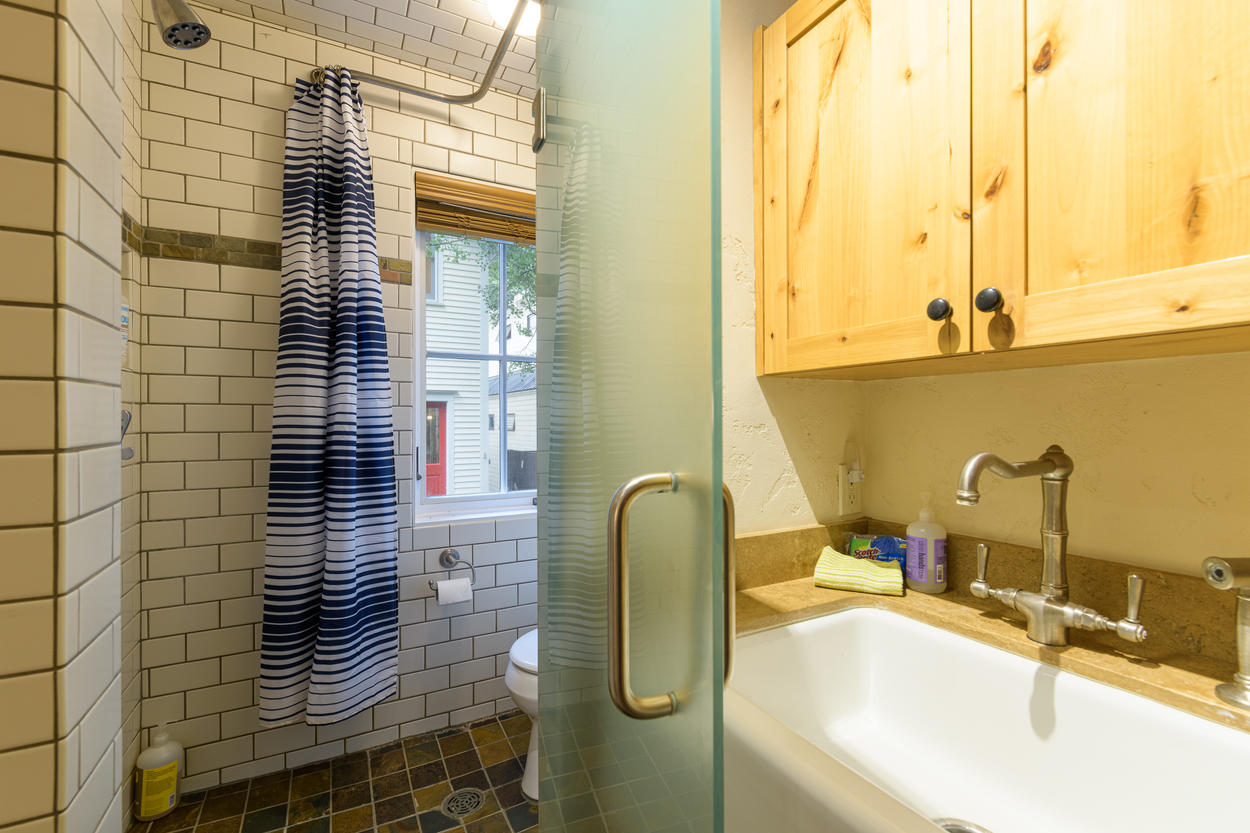 The guest home has a walk-in shower and bathroom area, and a sink in the kitchenette.