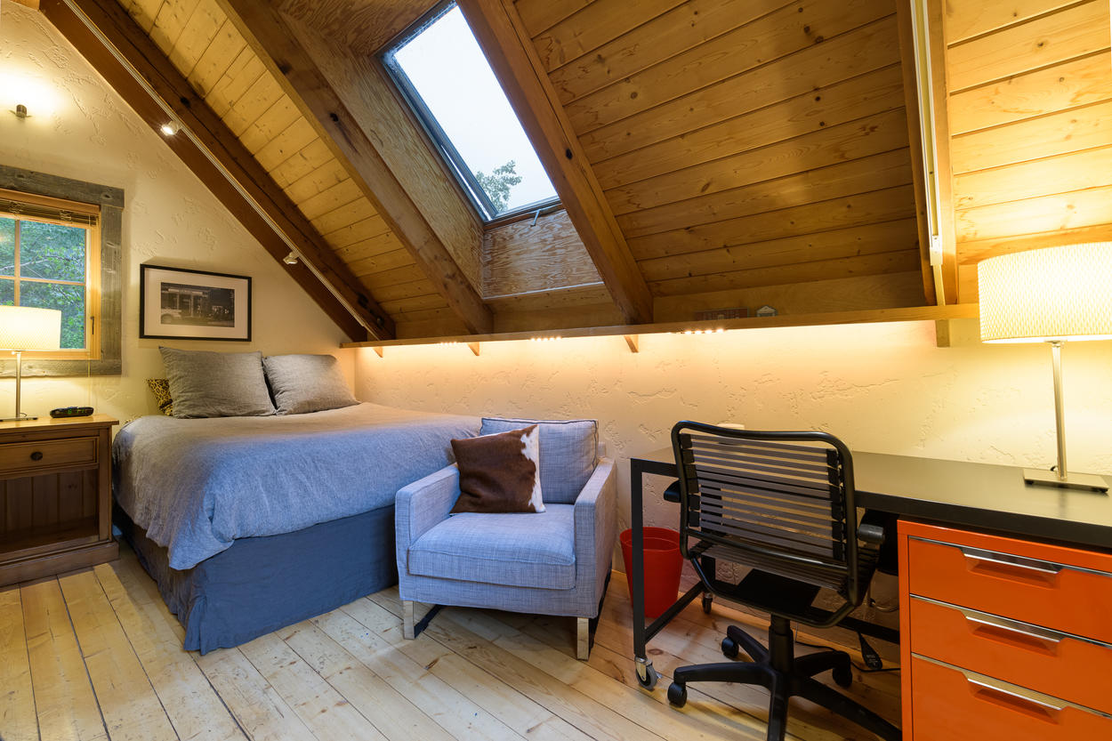 The guest house loft bedroom has a queen-size bed under a skylight.