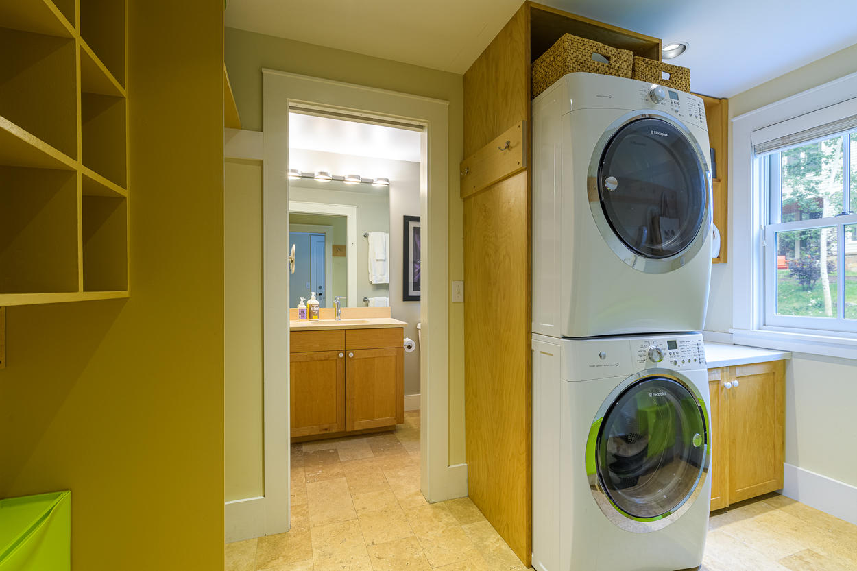The laundry room is located just off from the 1st level shared bathroom.