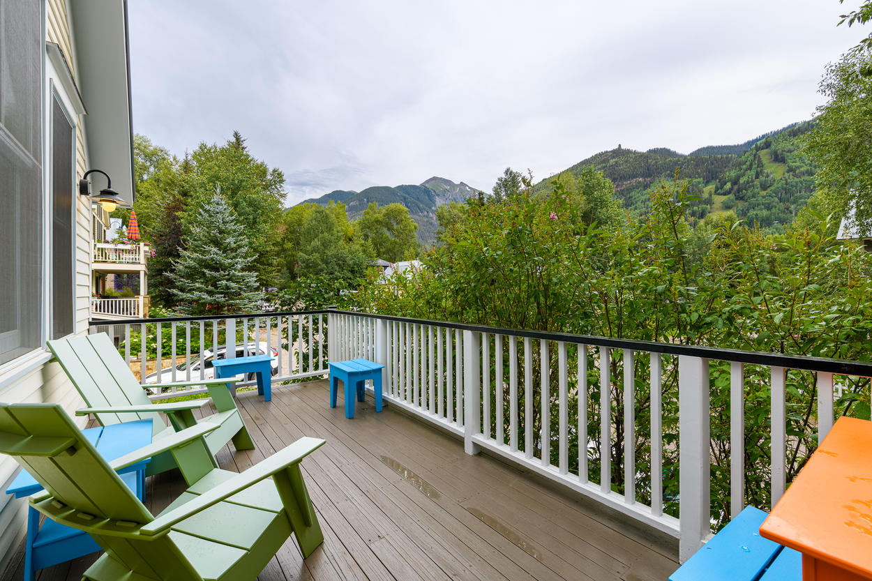 The front deck has seating and views of the peaks and ski runs in the distance.