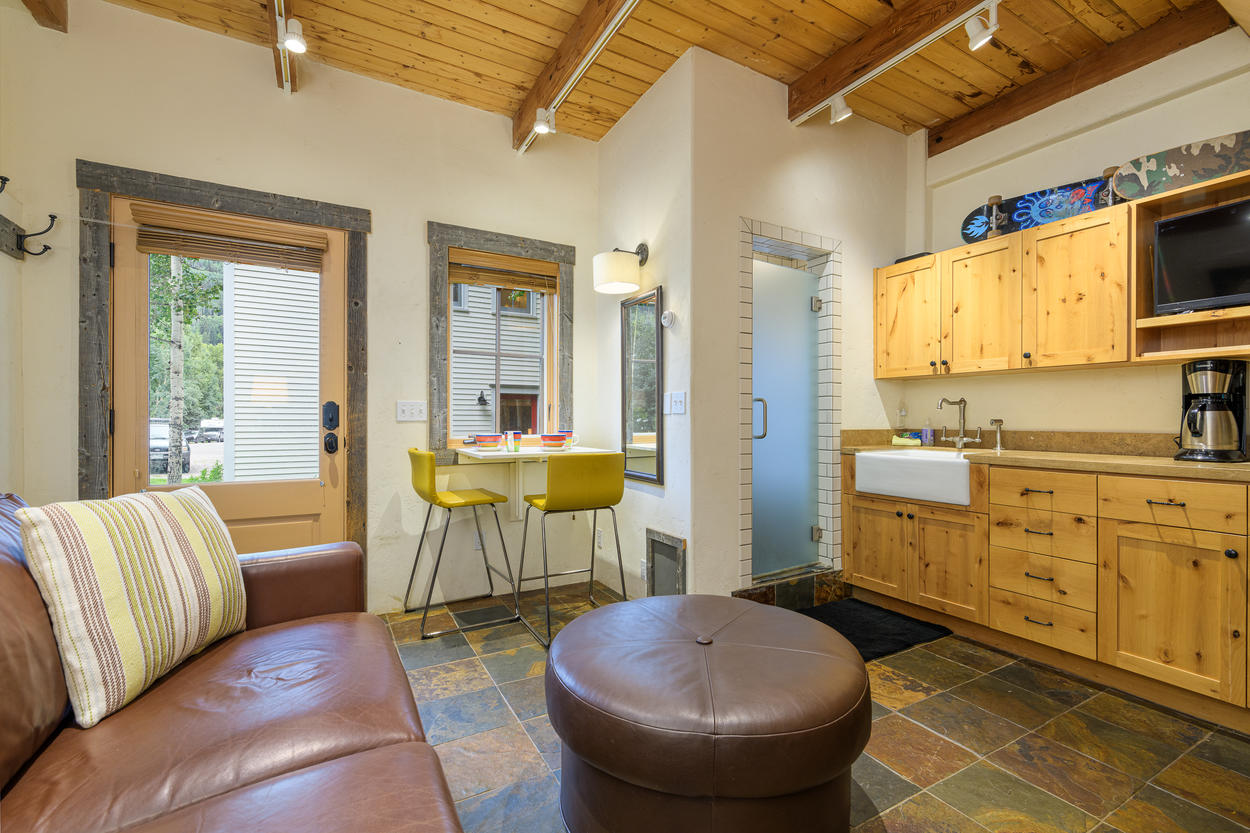 The guest house has its own kitchenette, dining table, and walk-in shower.