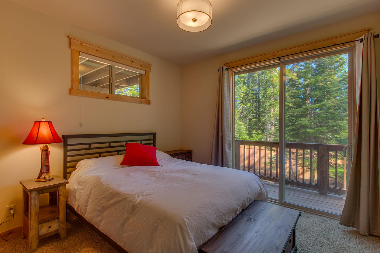 A private, cozy bedroom for those who like solitary moments, the lower level guest bedroom has a queen-size bed and a sliding door that opens onto the deck.