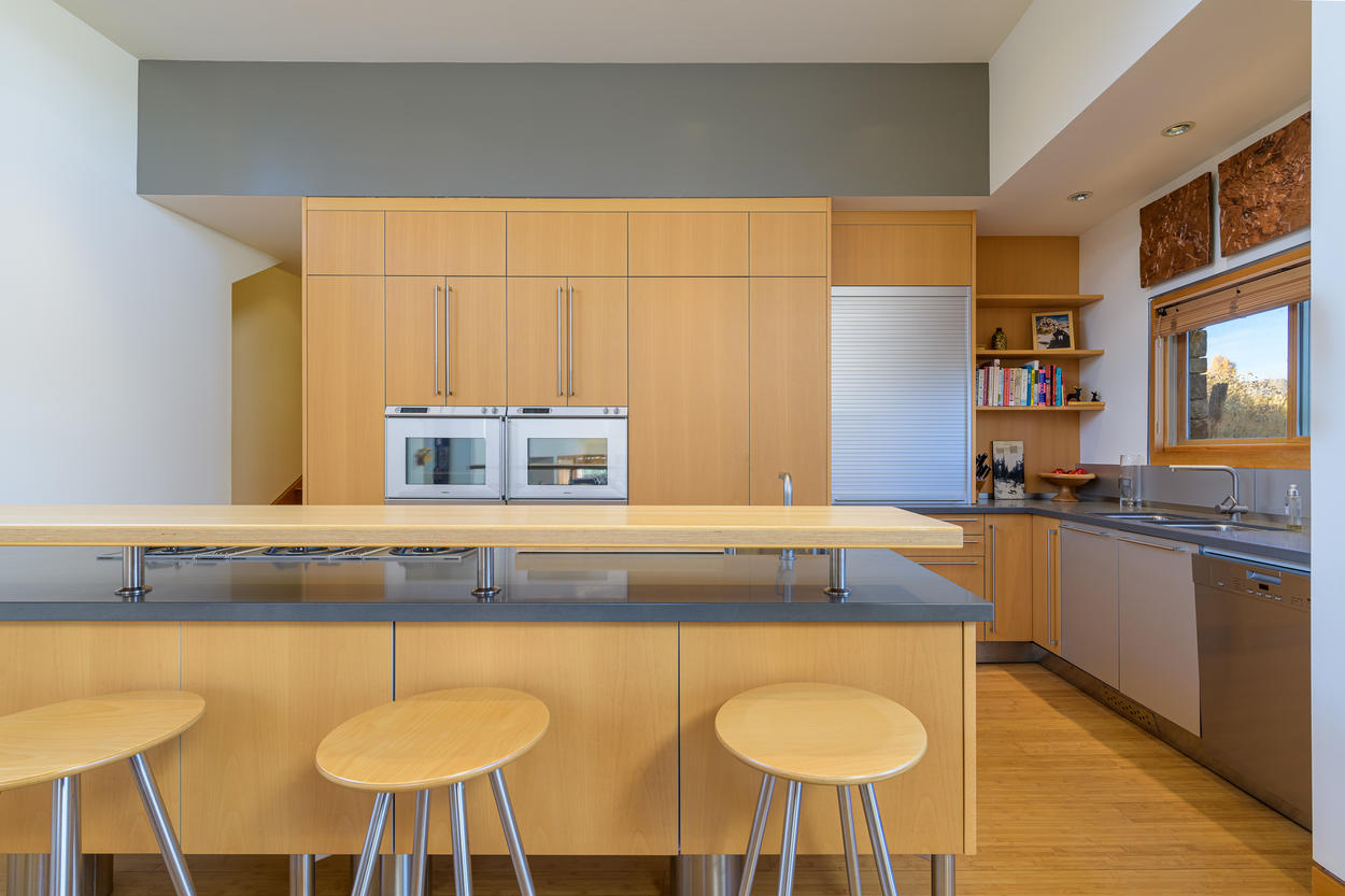 The kitchen has a sleek modern breakfast bar with seating for three guests.