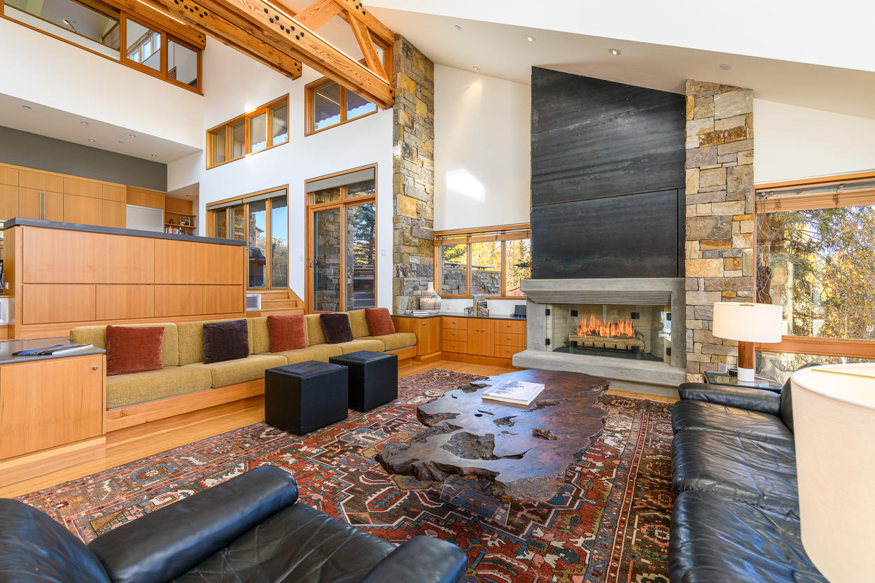 The room features a large glass gas fireplace, and a TV hidden behind the black panel above it.