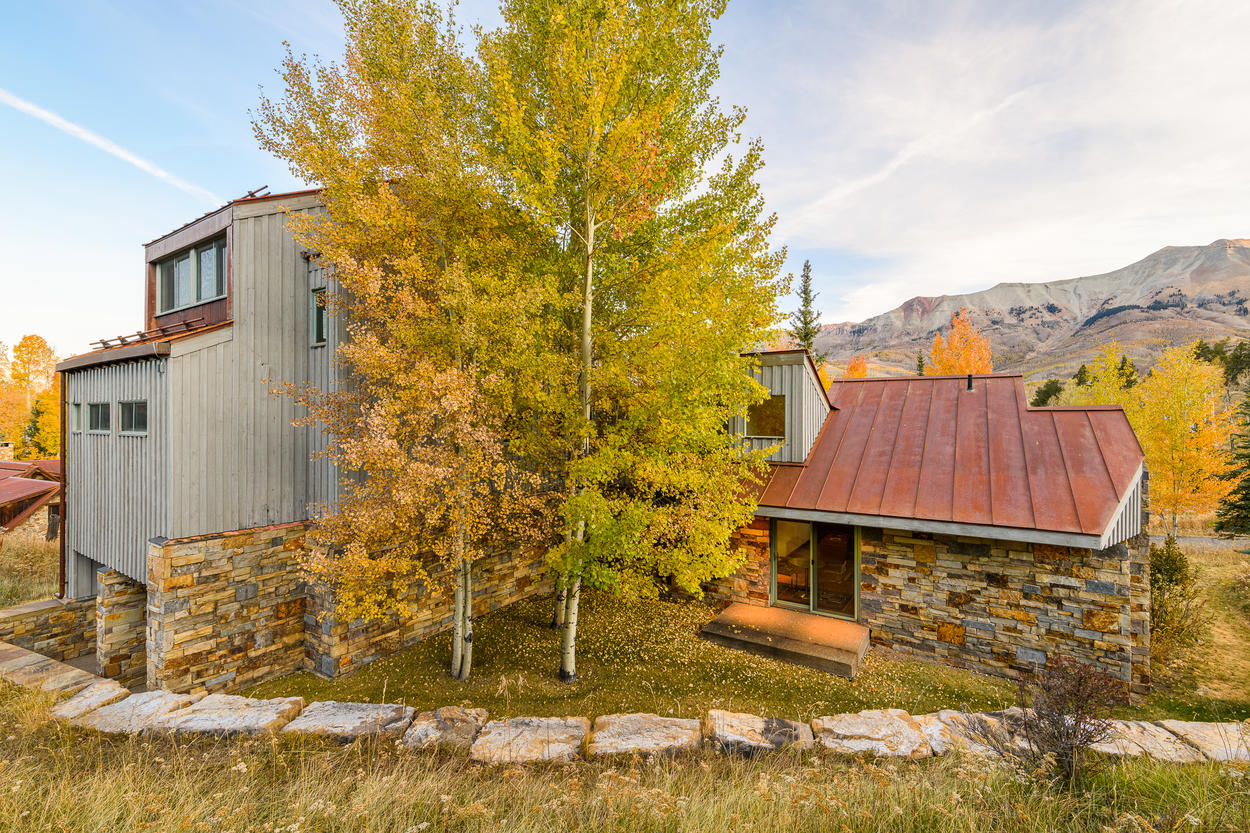 A low stone wall surrounds the back of the home.