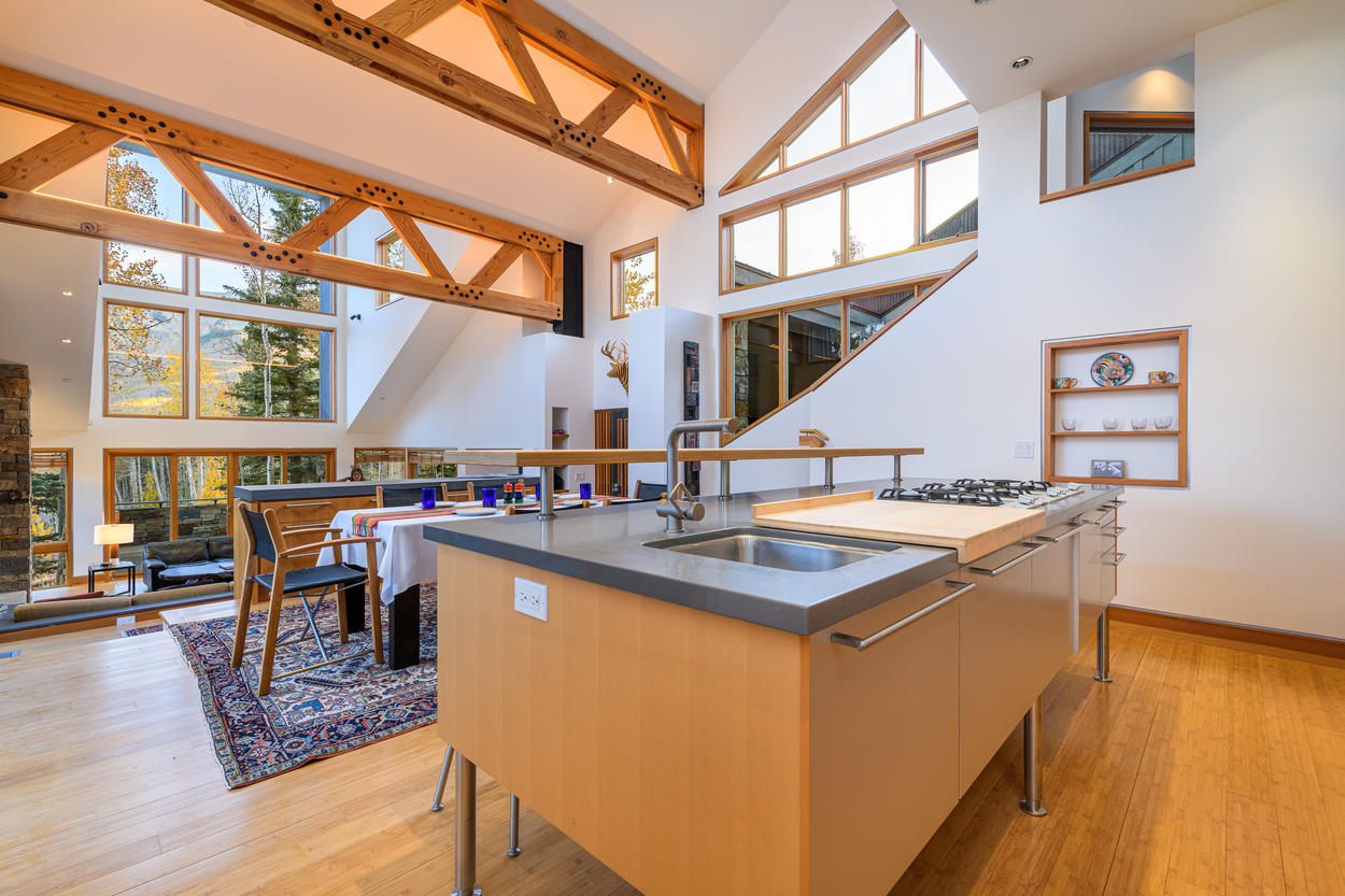 The dining table and kitchen are a part of the open-concept design, up just a few steps from the living area.