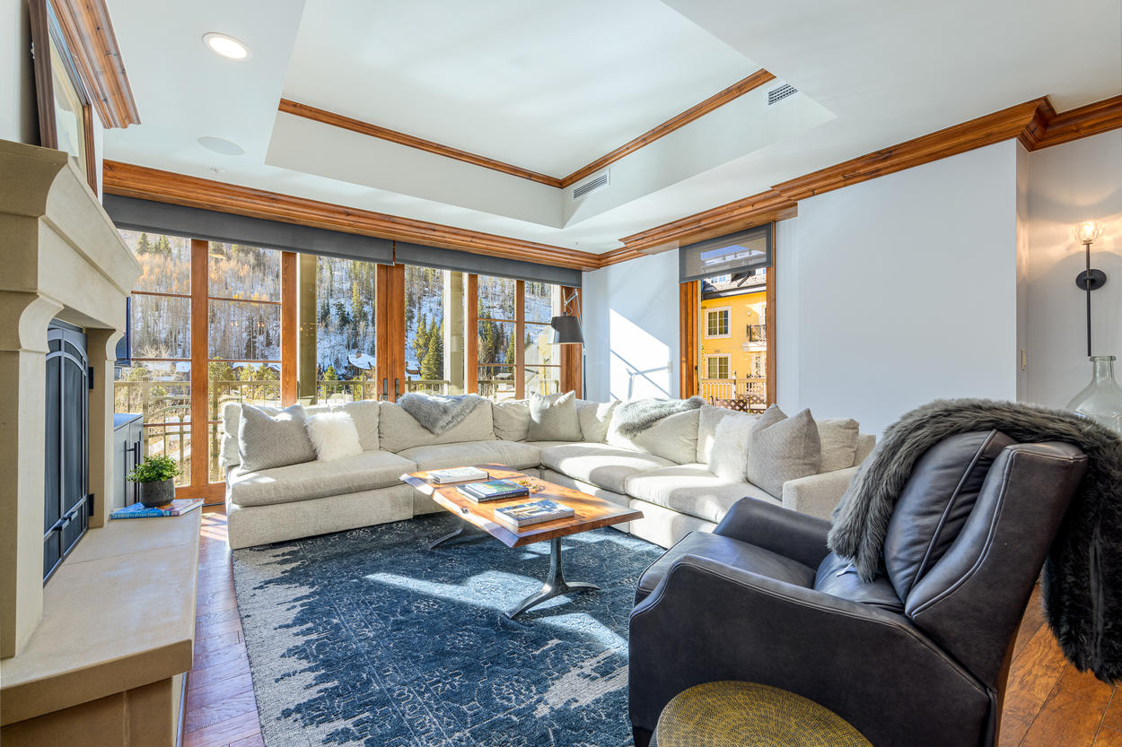 The living room features a TV, a large gas fireplace, and access to the private balcony.